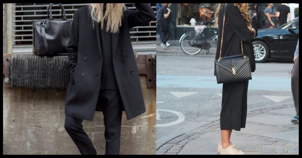 Two girls wearing all black outfits. One is wearing a long jacket and the other is wearing shot tailored pants.