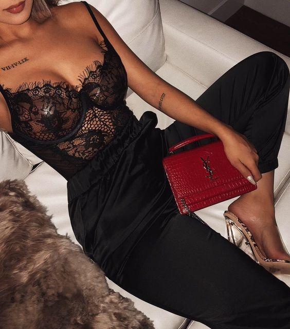 Women wearing a sexy black lace bodysuit with black pants and a red purse. It is an amazing night out outfit