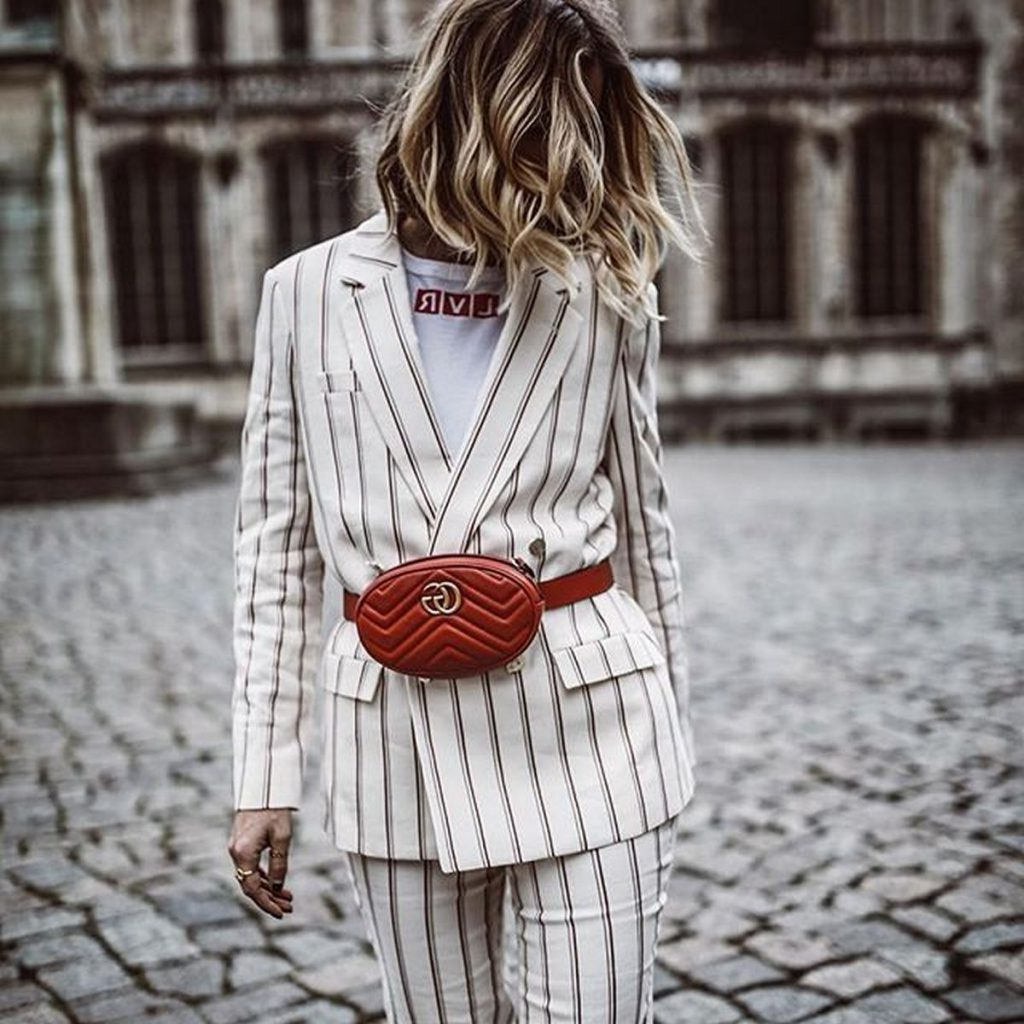 Girl wearing a white blazer with a Fanny Pack
