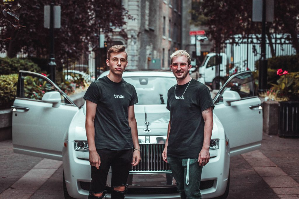 Two-hypebeasts-with-expensive-outfits-standing-in-front-of-a-rolls-royce-car-for-a-how-much-is-your-outfit-worth-video